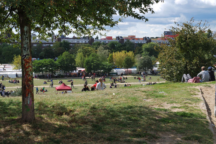 People relaxing in the grass above the Mauerpark Sunday flea market