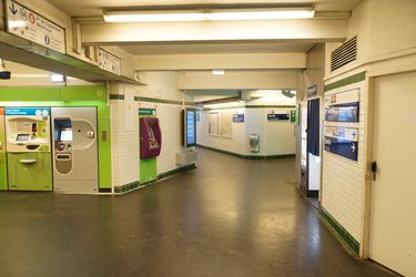Signage and ticket vending machines inside a Paris Metro Station