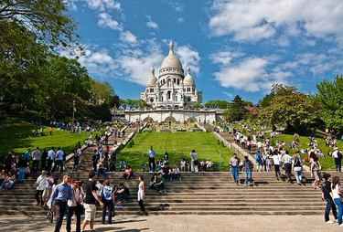 Many people enjoying a gorgeous day on the slopes and stairs leading up to Sacré Coeur