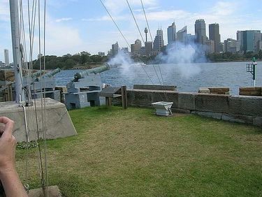 The One O'clock Gun fires from Fort Denison with a view of Sydney in the background