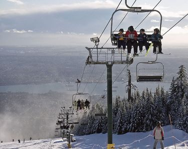 Enjoying spectacular views of the city along with winter sports on top of Grouse Mountain