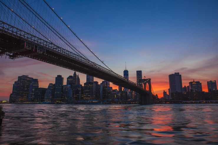 The Brooklyn Bridge stretches towards Manhattan and a beautiful sunset