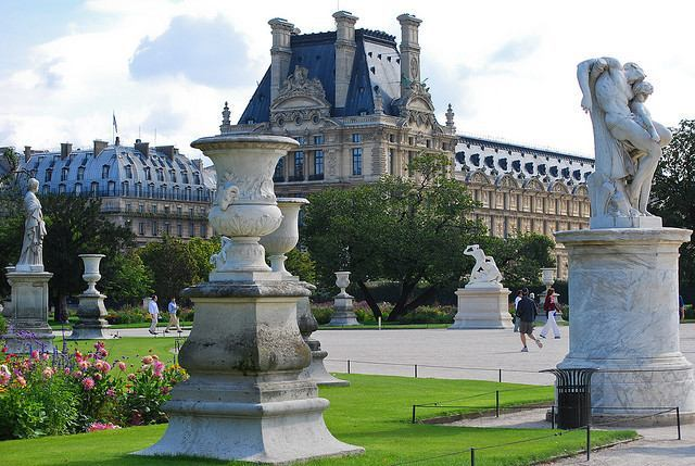 Statues and flowers backed by the Louvre Palace at Jardin des Tuileries