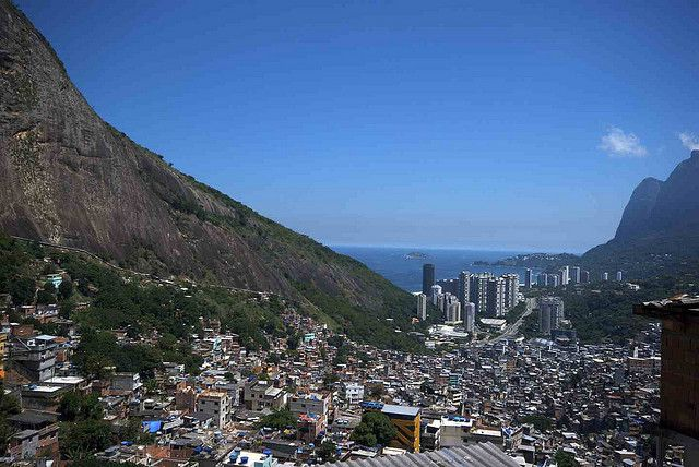 A favela spills down the hillside where it suddenly gives way to the oppulent highrises by the water