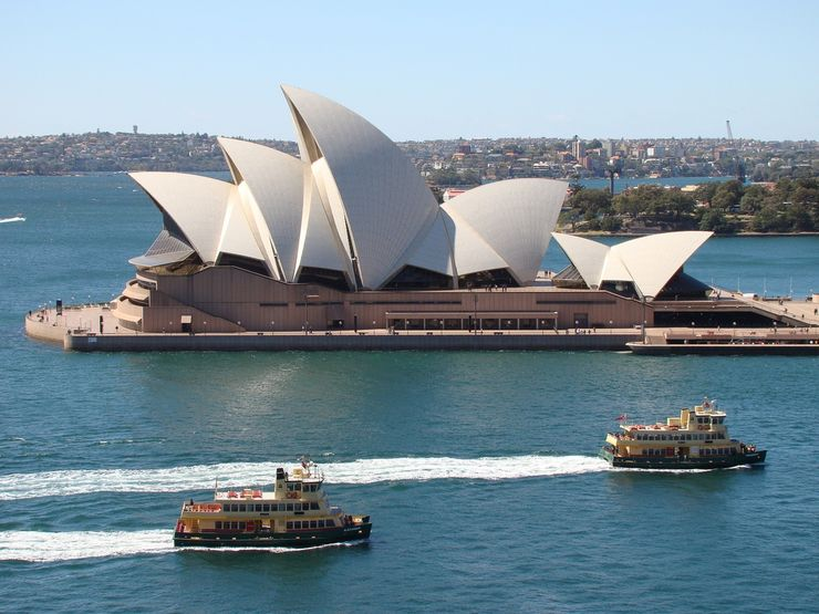 Two Sydney Ferries pass the Sydney Opera House as they approach Circular Quay
