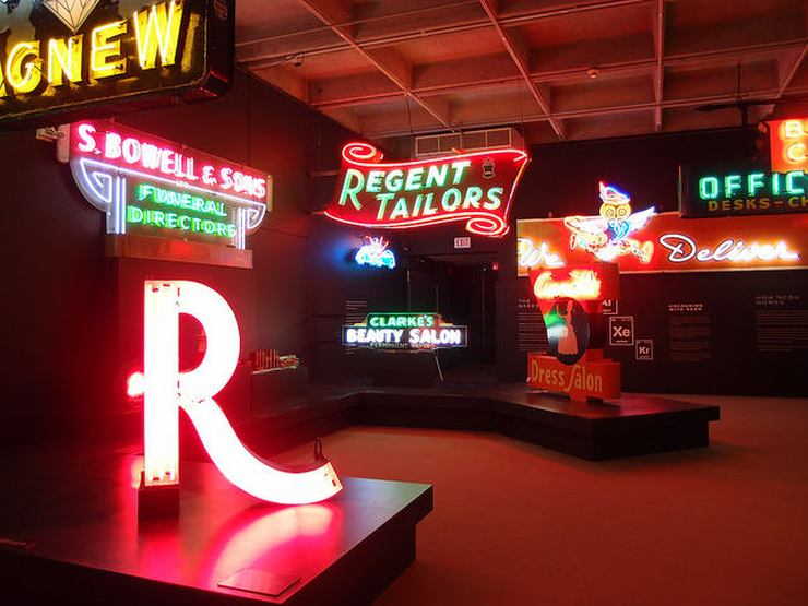 A display of brightly lit neon signs on display at the MOV